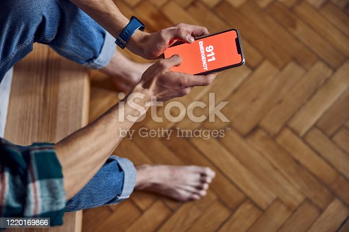 istock Male hands holding smartphone with 911 on screen 1220169866