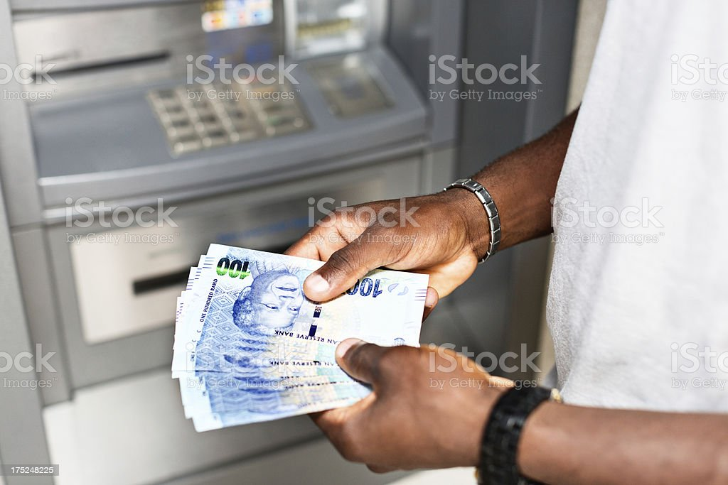 Male hands holding South African banknotes at ATM stock photo