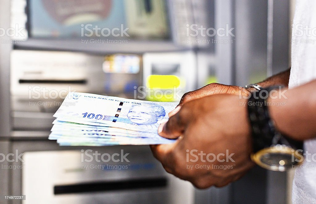 Male hands holding South African banknotes withdrawn from ATM stock photo