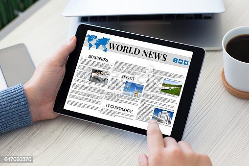 istock male hands holding tablet computer world news table notebook phone 647060370