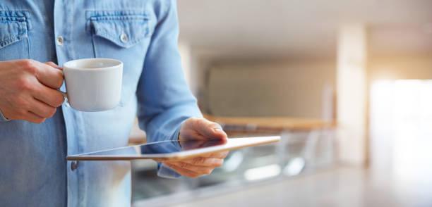 Hombre de las manos sosteniendo la tableta digital blanco y taza de café - foto de stock
