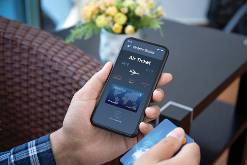 male hands holds phone with airplane ticket application airlines on the screen and credit card in the room