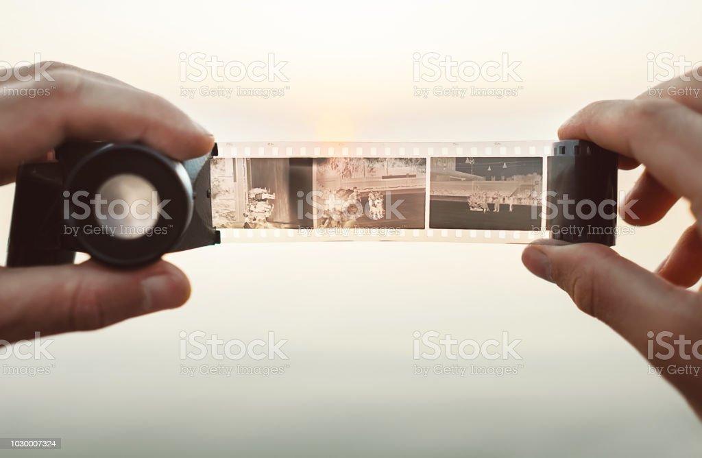 Männliche Hände Bild mit der alten Vintage 35mm Film Negative Viewer um zu sehen, einen Rahmen auf dem Sonnenuntergang Hintergrund – Foto