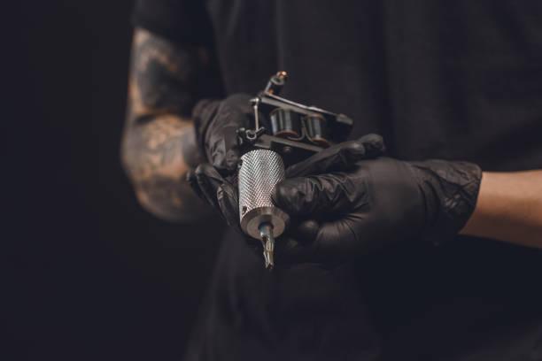 mannelijke handen in handschoenen houden tattoo machine geïsoleerd op zwart - tatoeage stockfoto's en -beelden