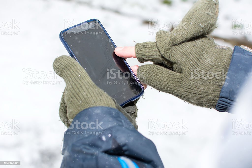 Male hands in gloves using a smartphone stock photo