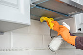 istock male hands in protective gloves cleaning the kitchen hood with rag and spray bottle 1239296227
