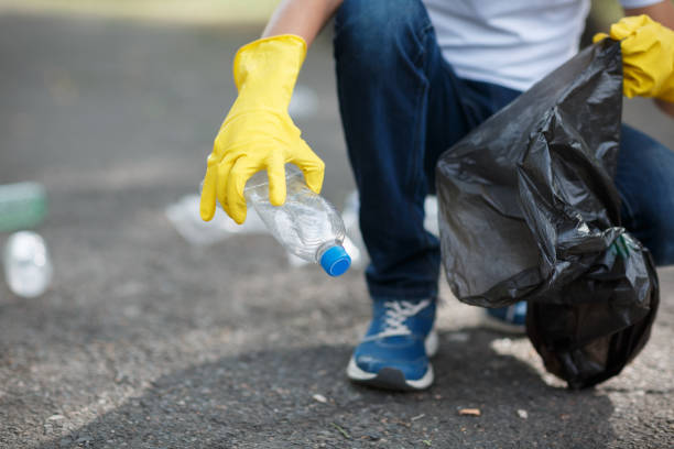 Male hands in yellow rubber gloves putting household waste into small and black bin bag outside. Hands in yellow gloves picking up empty of bottle plastic into bin bag on asphalt, volunteer and purity concept. Enviromental protection. environmental cleanup stock pictures, royalty-free photos & images