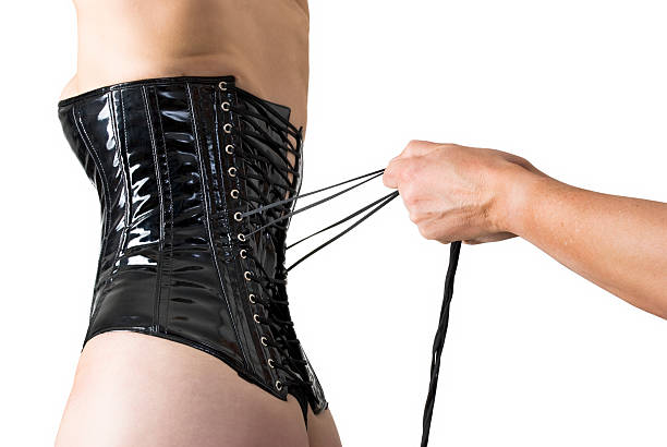 Male hands lacing back of a corset.  corset stock pictures, royalty-free photos & images