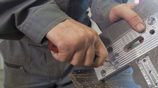 Male hands makes chamfering removing burrs on metal panel with a scraper, close up