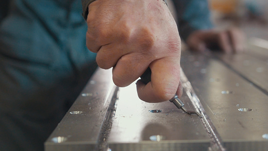 Worker with a scraper chamfering removing burrs on metal object for manufacturing industrial CNC machines, close up
