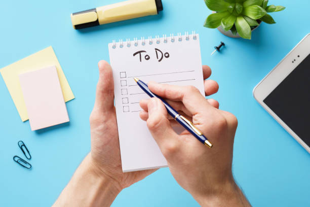 male hands making a to-do list in a notebook over an office desk - to do list foto e immagini stock