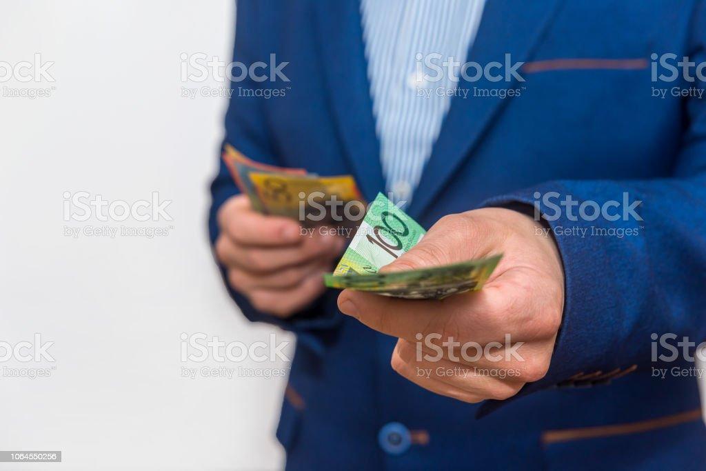 Male hands offering australian dollar banknotes, macro stock photo