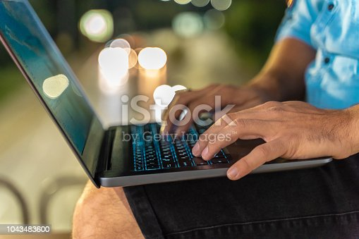 Male hands on laptop keyboard outdoors at night defocused city traffic in the background. The male is of caucasian ethnicity has short brown hair and is casually dressed in blue shirt with short sleeves. The scene is situated in downtown district in Sofia, Bulgaria (Eastern Europe) during night time. The picture is taken with Sony A7RIII camera.