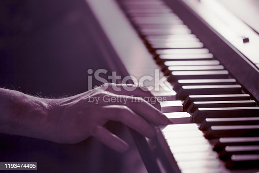 male hands on the piano keys closeup of a beautiful colorful background, the concept of musical activity