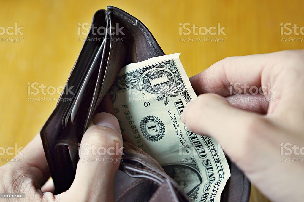 Male hands opening almost empty leather wallet with one Dollar stock photo