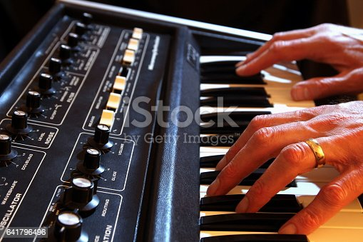 istock Male hands playing a vintage analogue synth in shallow focus 641796496