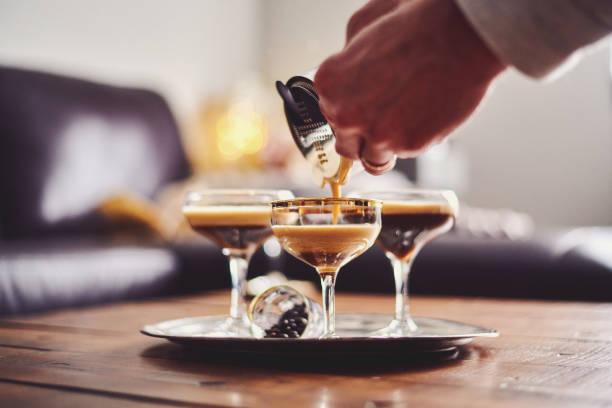 männliche hände gießen espresso martini cocktail in glas - espresso stock-fotos und bilder