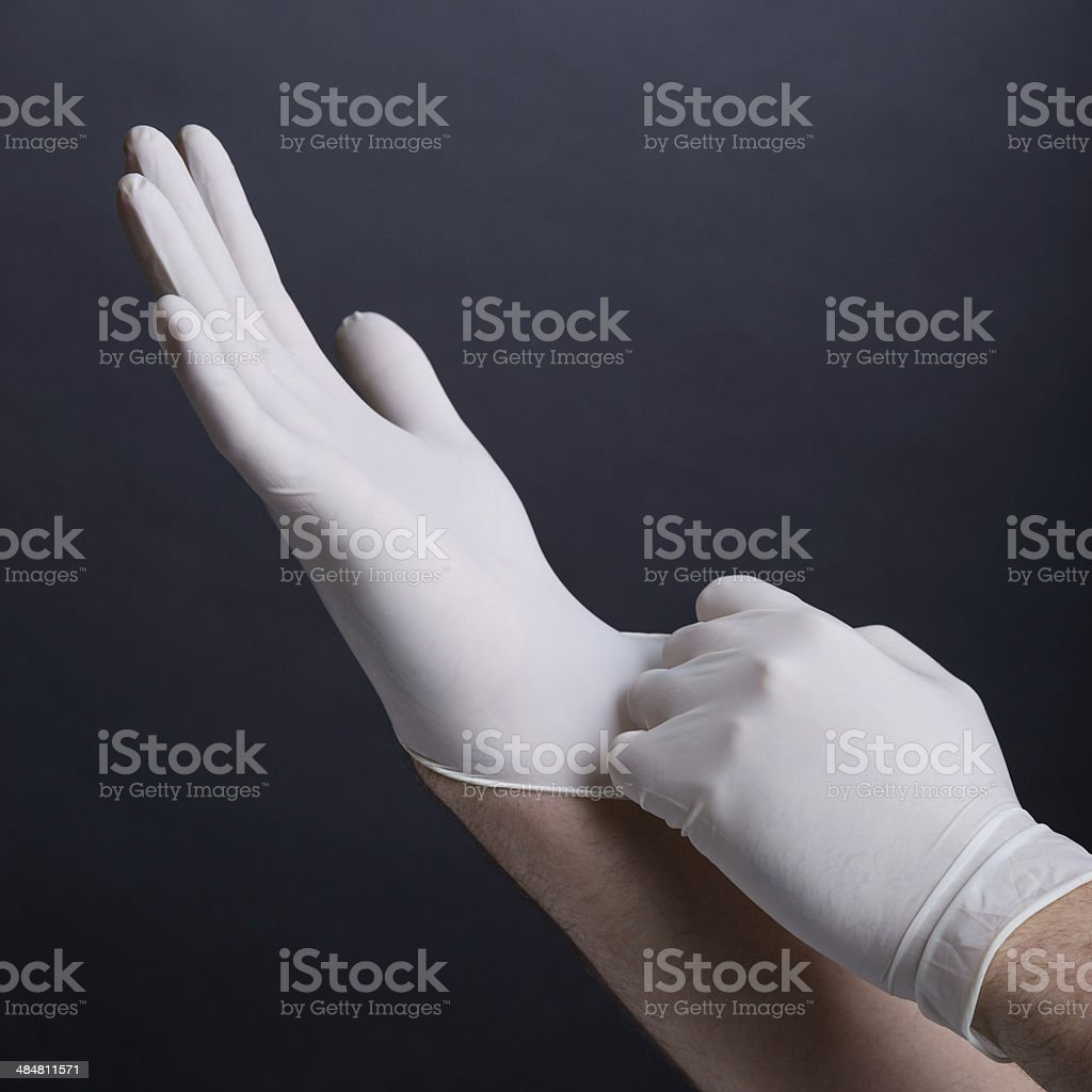 Male hands putting on latex gloves stock photo
