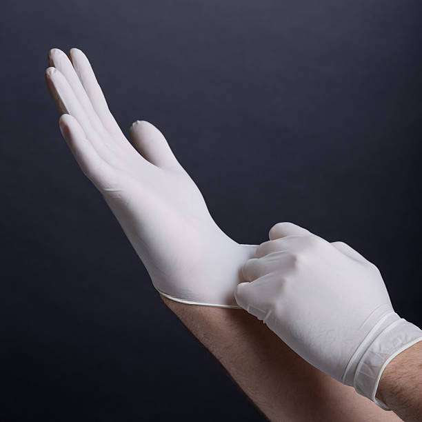male hands putting on latex gloves - latex stock pictures, royalty-free photos & images