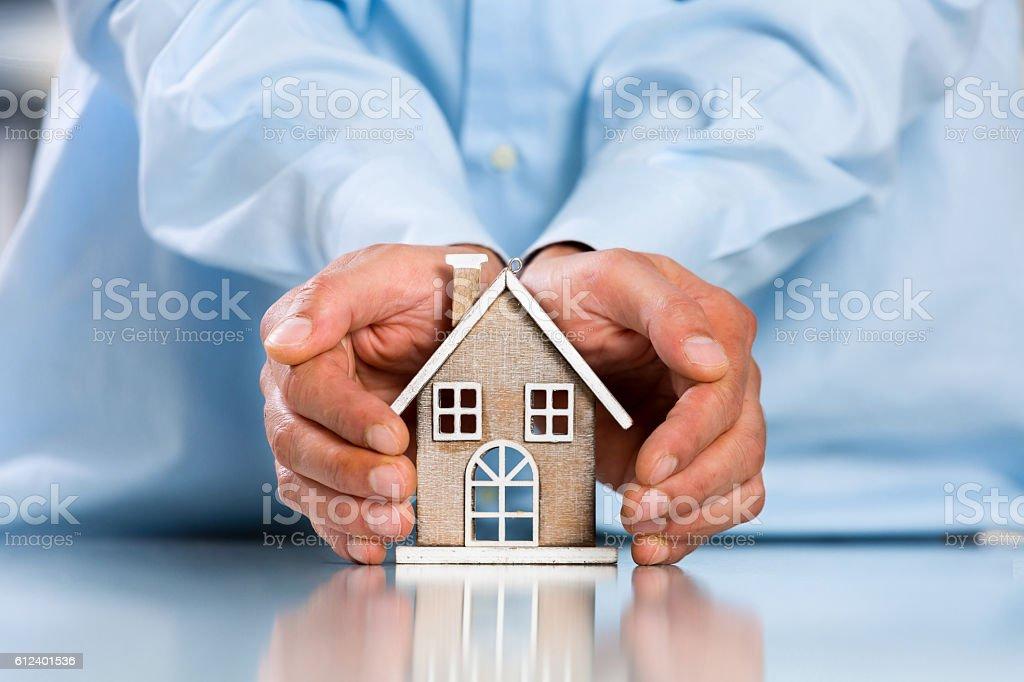 Male hands saving Miniature House royalty-free stock photo