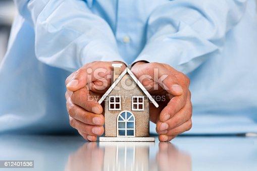 Male hands saving Miniature House on Desktop. Insurance Concept. Insulation Concept