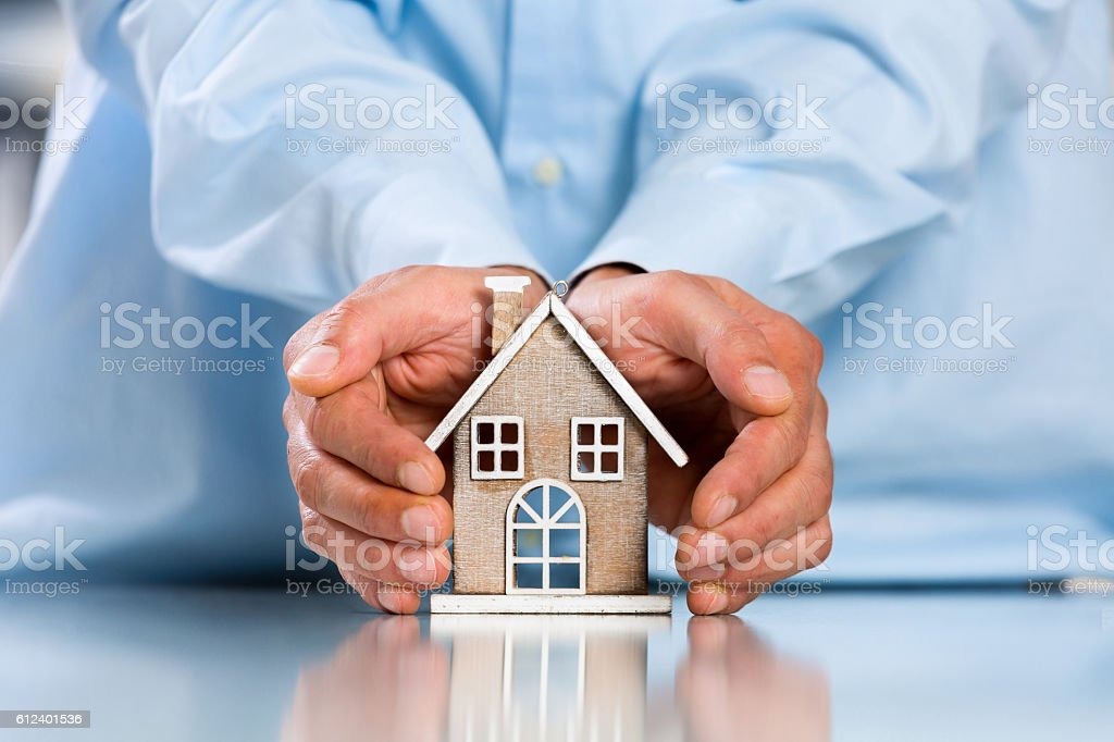 Male hands saving Miniature House stock photo