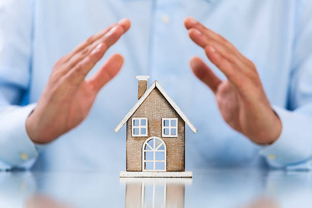 Male hands saving Miniature House stock photo
