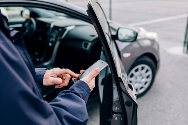 Male hands typing on cell phone. Unrecognizable mature man standing at rental car with smartphone. stock photo