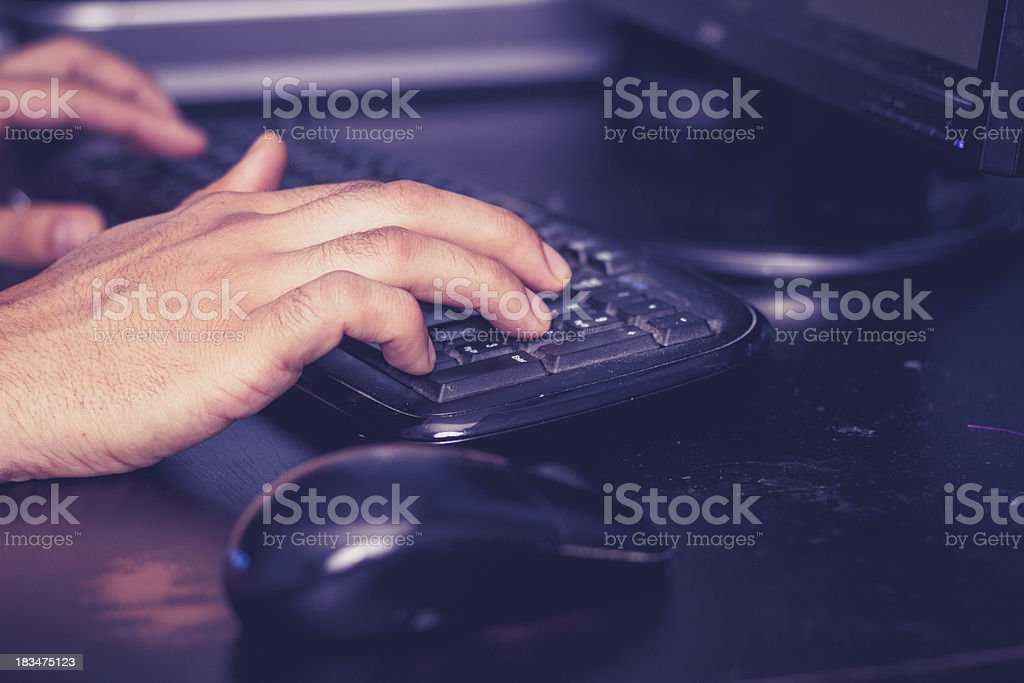 Male hands typing on keyboard at desk royalty-free stock photo