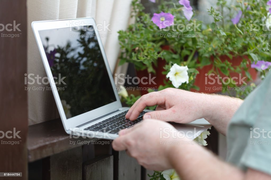 Male hands typing on laptop in the park stock photo