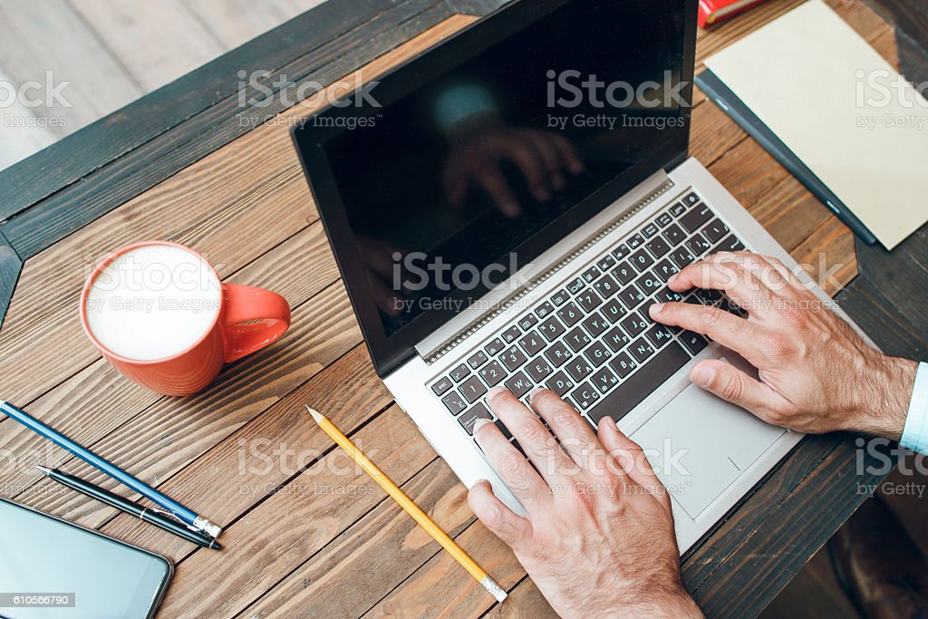 Male hands typing on laptop keyboard, mockup stock photo
