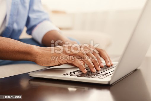 Working at laptop pc. Close up image of male hands typing text or programming code in computer at home