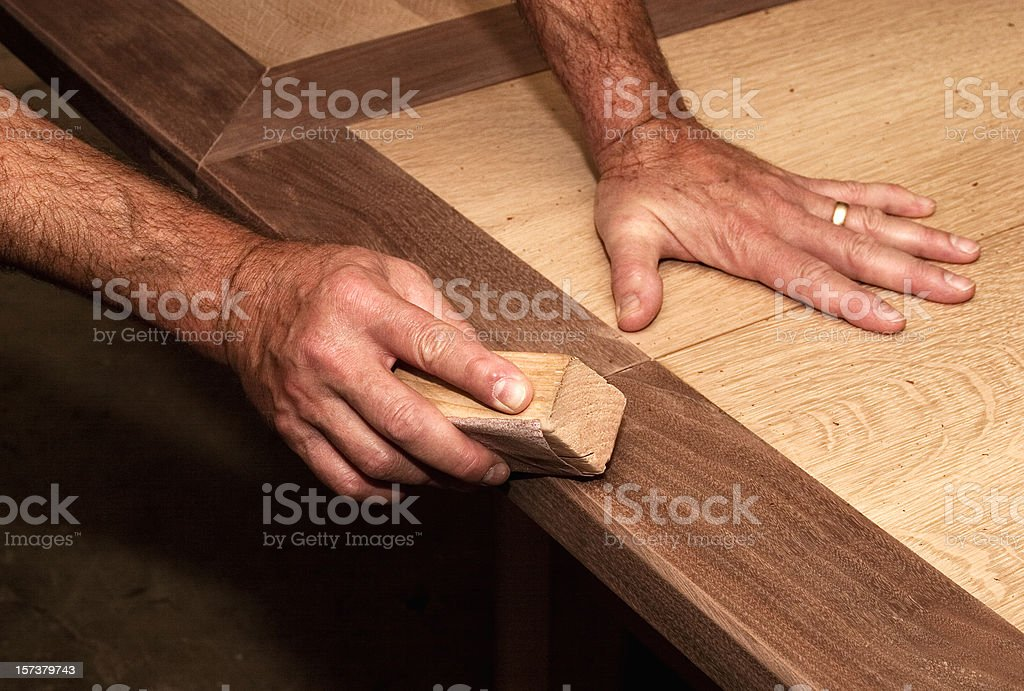 Male hands using a sanding block on some wood royalty-free stock photo