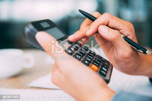 istock Male hands using calculator_tone 662607502