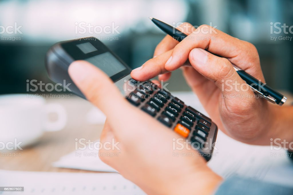 Male hands using calculator_tone stock photo
