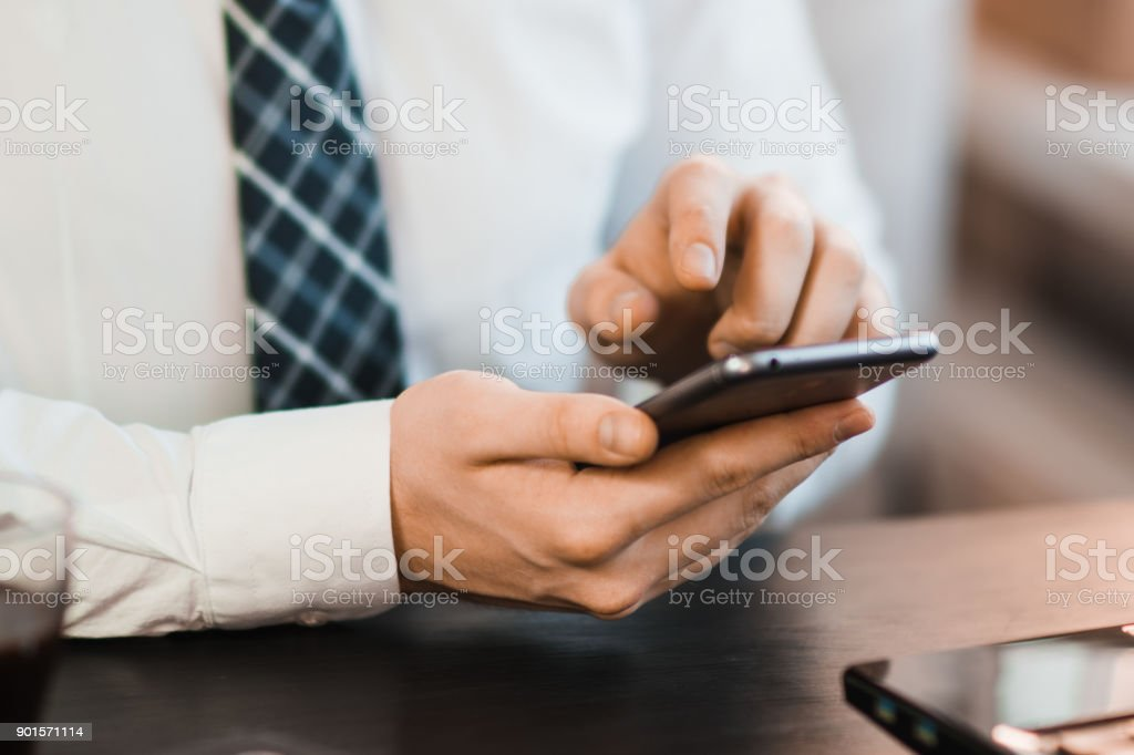 Male hands using smartphone with abstract financial charts and map over office desktop stock photo