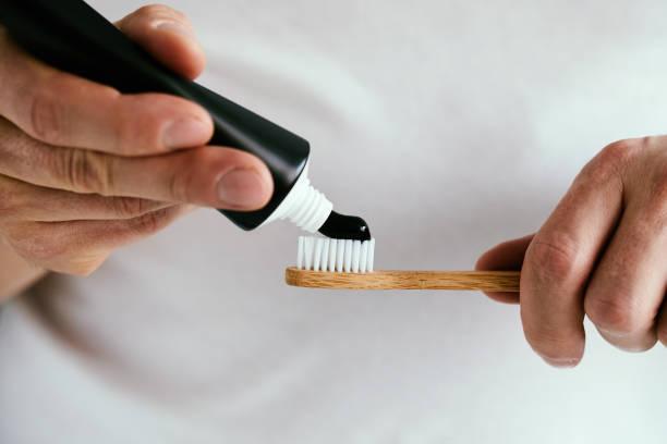 Manos masculinas con una dentífrica negra y un cepillo de bambú - foto de stock