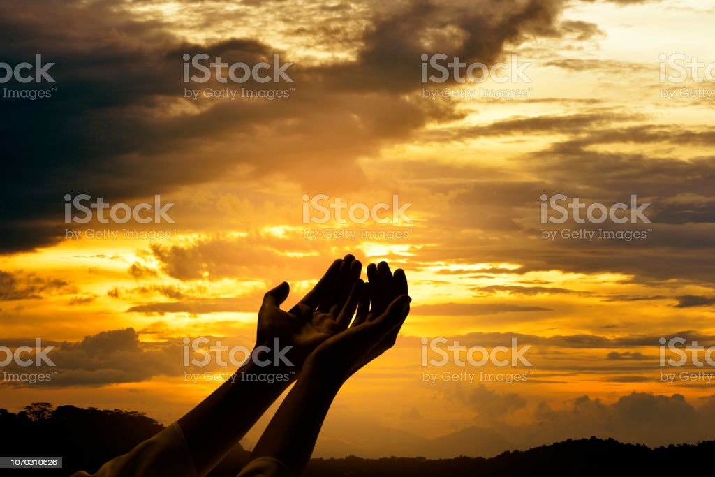 Male hands with open palm praying to god over sunrise background