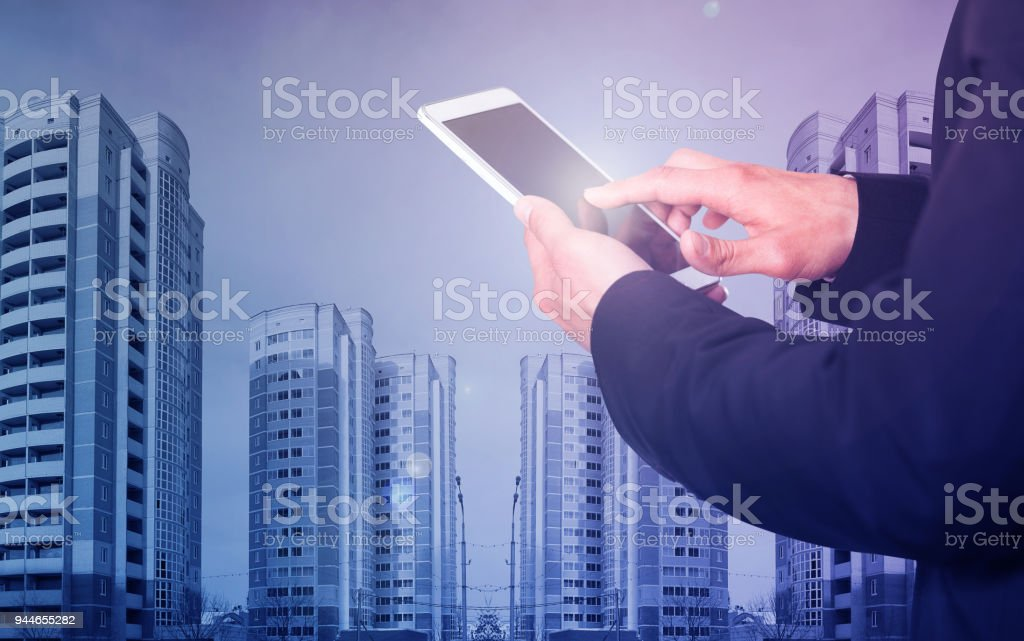 Male hands with phone on skyscraper background stock photo