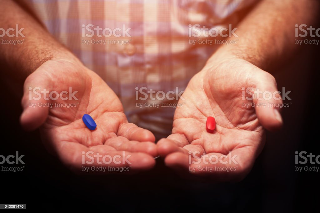Male hands with red and blue pills stock photo