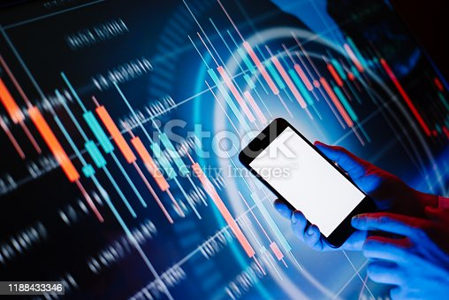 641839870 istock photo Male hands with smartphone in front of a digital display with financial information. Blank empty screen. Mock up 1188433346