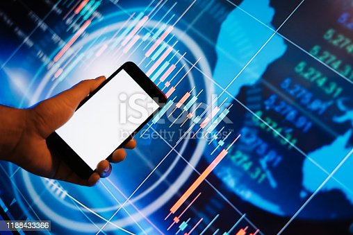 641839870 istock photo Male hands with smartphone in front of a digital display with financial information. Blank empty screen. Mock up 1188433366