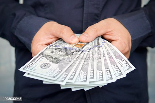 male hands with wrist watch is considered American dollars. Hands holding dollar cash. 1000 dollars in 100 bills in a man's hand close-up on a dark background. hundred