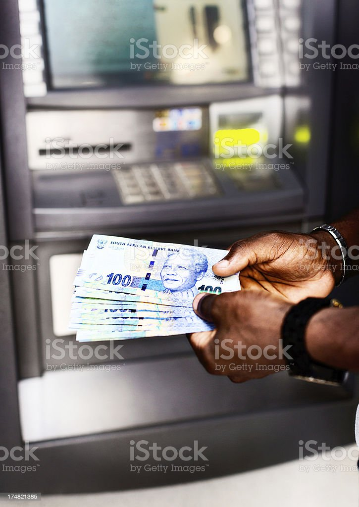 Male hands withdrawing South African Hundred Rand banknotes from ATM stock photo