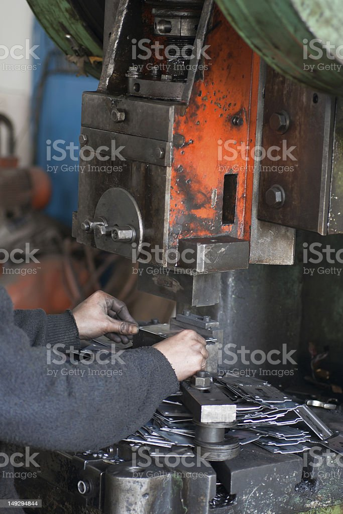 Male Hands Working on Eccentric Press stock photo