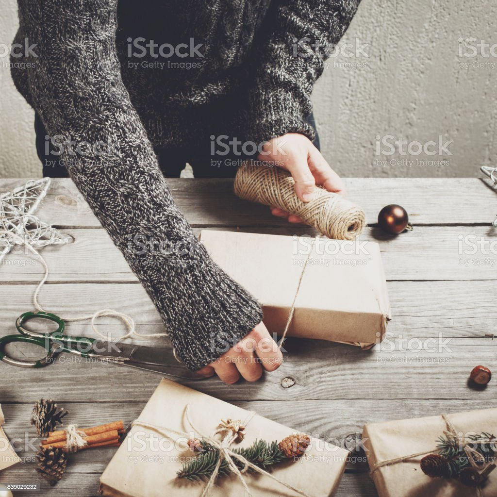 Male hands wrap christmas present on wooden table stock photo