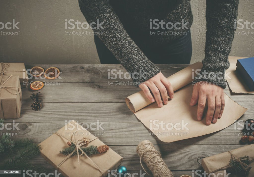 Male hands wrapping xmas present on wooden table close up stock photo