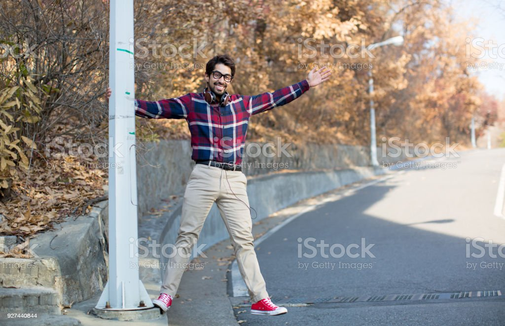 A Male Hanging and Extending on Pole with Arm and Leg Out. stock photo