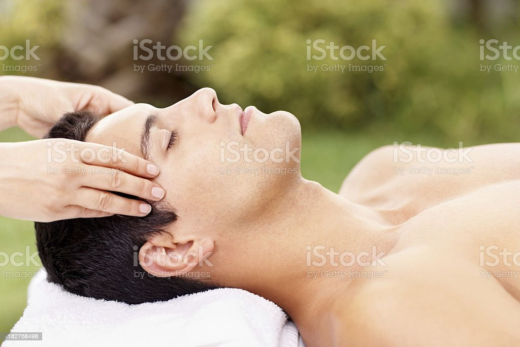 Male having a relaxing head massage at an outdoor spa royalty-free stock photo
