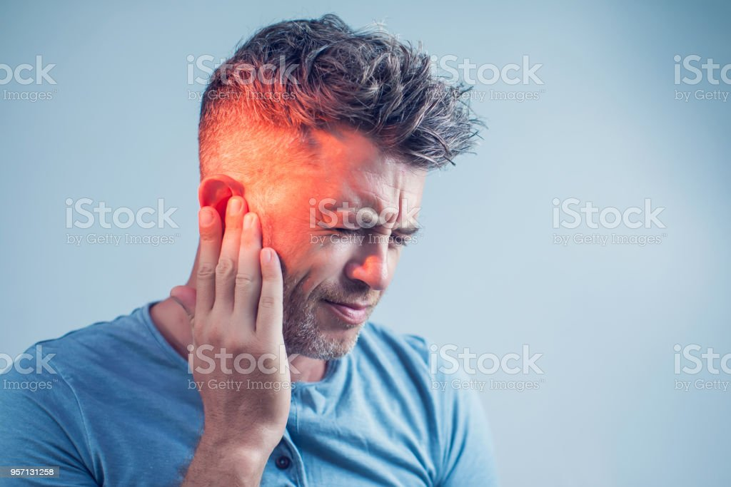 male having ear pain touching his painful head isolated on gray...